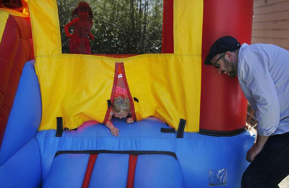 Shandel Story plays peek-a-boo with Helen Cunningham, 2, a friend's child, during the birthday party for his friend's son in Oakland. Photo: Leah Millis, The Chronicle