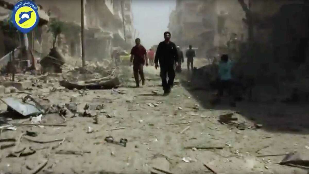 In this image made from video posted online by the Syrian Civil Defense White Helmets, people stand in rubble after airstrikes and shelling hit Aleppo, Syria, Sunday, April 24, 2016. Air strikes and shelling pounded Aleppo for a third straight day Sunday, killing two young siblings and more than a dozen others in Syria's largest city and former commercial capital.