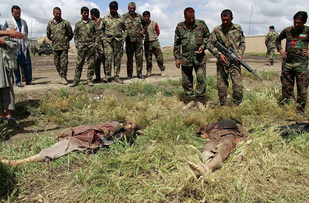 Afghan National Army (ANA) soldiers stand over the bodies of Taliban militants after clash between the Taliban and Afghan security forces in Kunduz province on April 17, 2016. Afghan security forces drove Taliban fighters back from Kunduz city, officials said, as the insurgents began the 2016 fighting season by targeting the northeastern provincial capital they briefly captured last year. / AFP / NASIR WAQIF