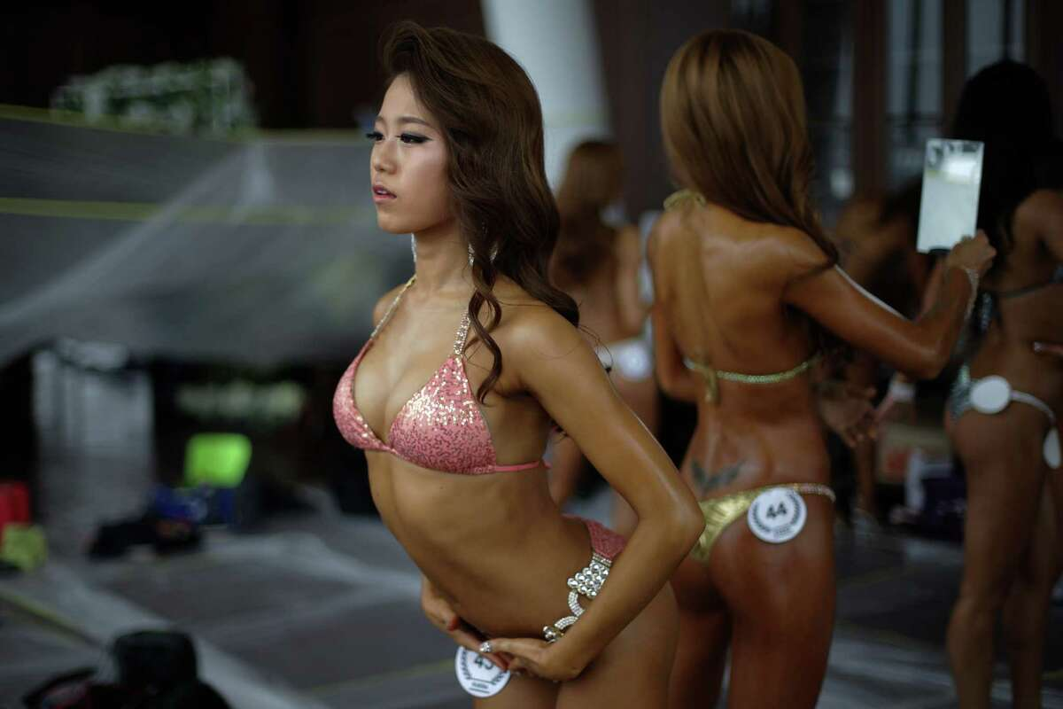 SEOUL, SOUTH KOREA - APRIL 17: Female bodybuilders prepare themselves for judging backstage during the NABBA/WFF Asia-Seoul Open Championship on April 17, 2016 in Seoul, South Korea.