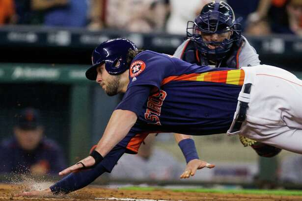 Houston Astros left fielder Jake Marisnick (6) stretches out to avoid a diving tag by Detroit Tigers catcher Jarrod Saltalamacchia (39) to score as the Astros take on the Tigers at Minute maid Park Sunday, April 17, 2016 in Houston.