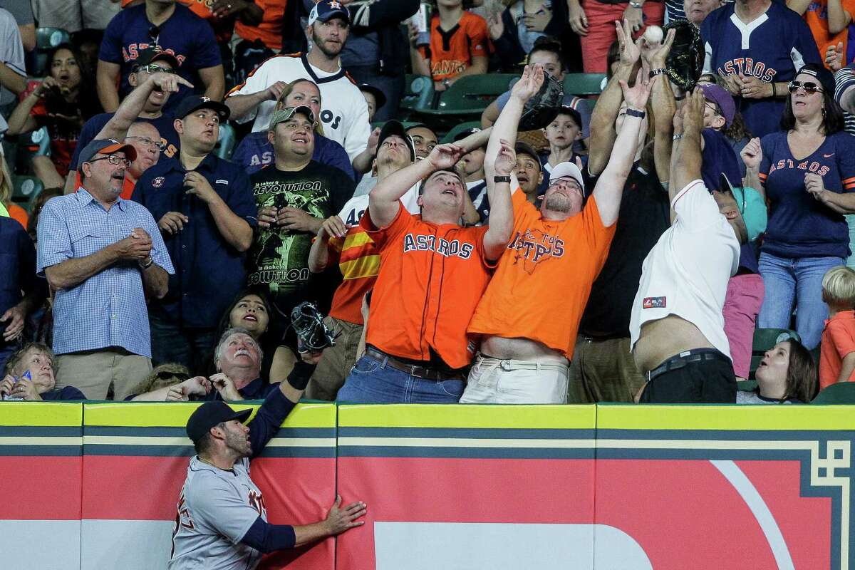 Detroit Tigers right fielder J.D. Martinez (28) hits the wall as fans grab a home run from Houston Astros second baseman Jose Altuve (27) in the first inning as the Astros take on the Tigers at Minute maid Park Sunday, April 17, 2016 in Houston.