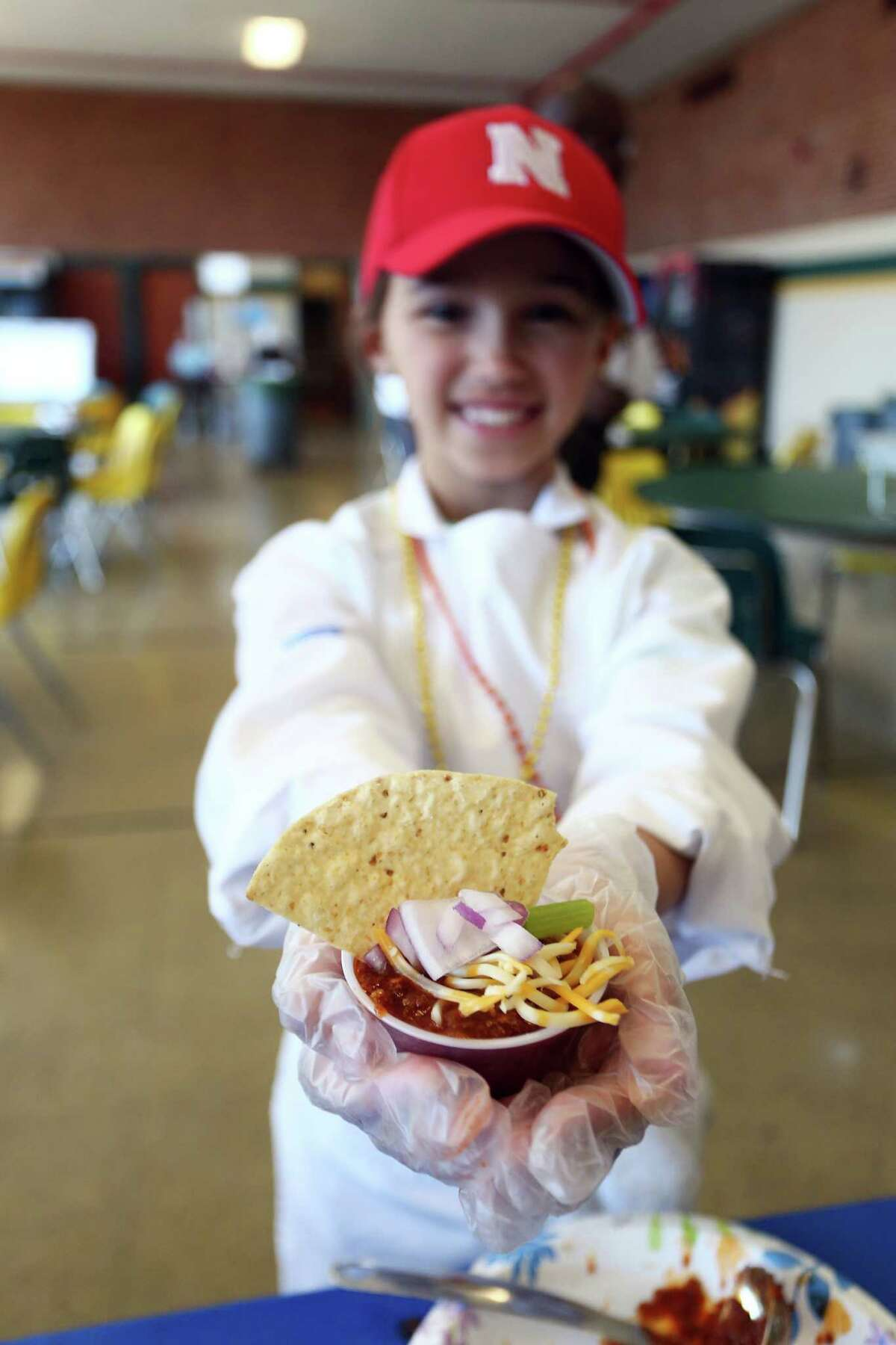 Seven-year old Alexis Adcock holds her team's submission, the properly named Daddy-Daughter Chili, at the Third Annual Charity Chili Cook-off at Trinity Catholic High School on Sunday, April 17, 2016.