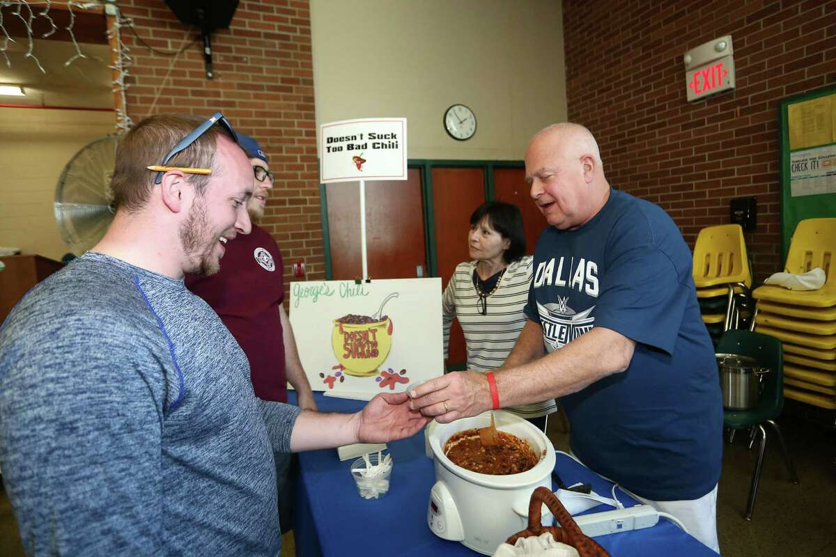 George Dallas, right, hands a serving of his 'Doesn't Suck Too Bad Chili' to Ken Holbert during the Third Annual Charity Chili Cook-off held at Trinity Catholic High School on Sunday, April 17, 2016. The charity cook-off was organized by the Exchange Clubs of North Stamford, Stamford and Norwalk to help prevent and stop child abuse in Fairfield County.