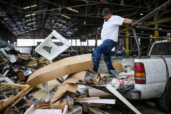 Lupe Cantu, kicks a large piece of styrofoam among other items, while emptying his truck of garbage, which will later be sorted at the Recology Center, in San Francisco, California, on Thursday, April 14, 2016.