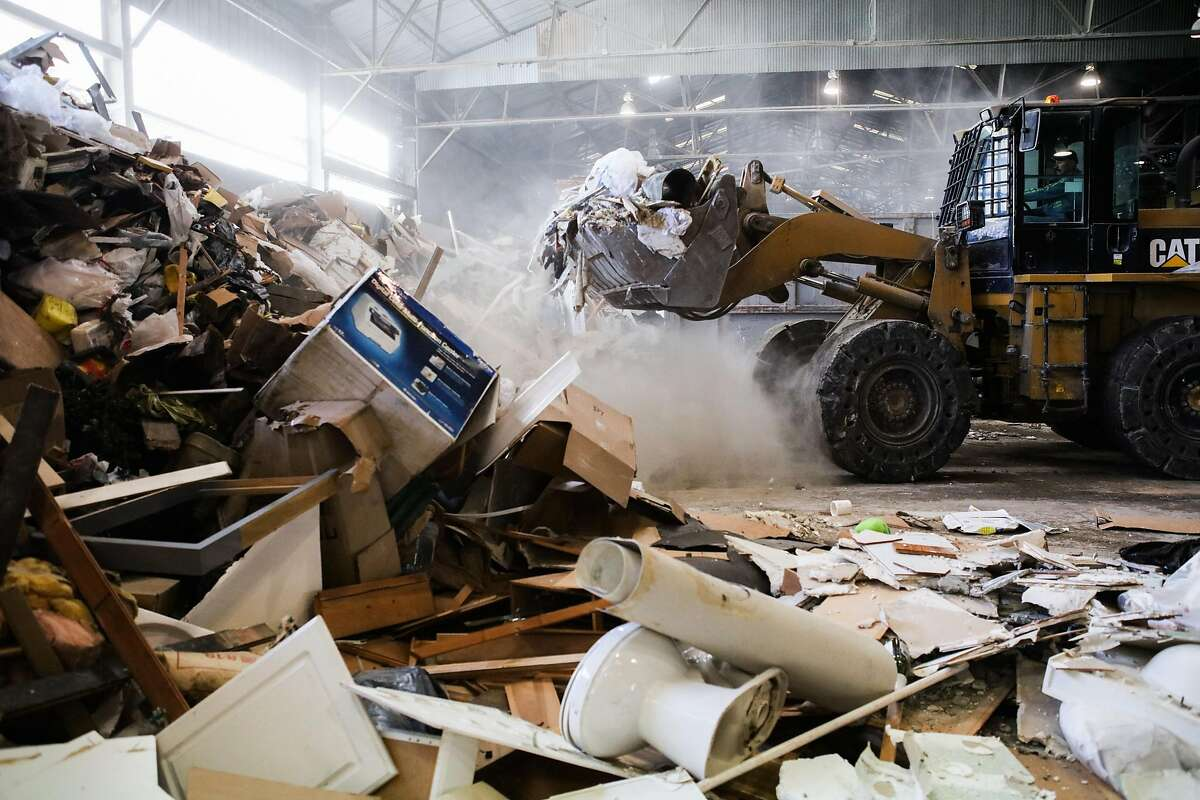 A loader picks up garbage to be sorted at the Recology Center in San Francisco , California, on Wednesday, April 14, 2016.