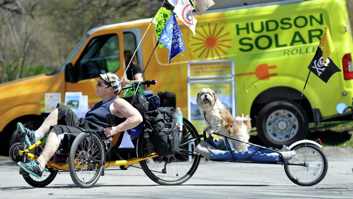Violet Leighton from Fultonville pedals her bike with the dog Boomer on the back during the Earth Day Expo on Sunday, April 17, 2016, in Albany, N.Y. (Paul Buckowski / Times Union)