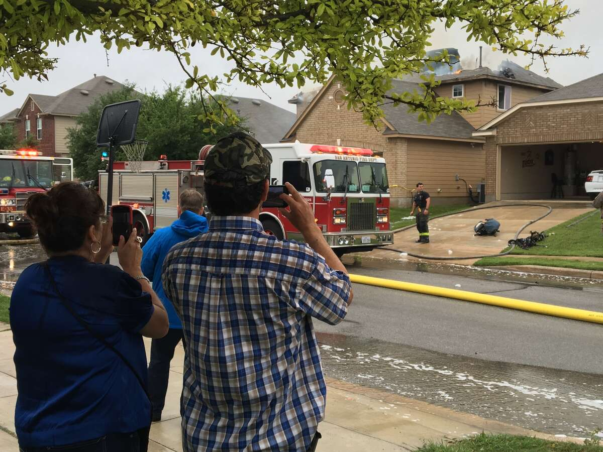 San Antonio firefighter fight a house fire on the far West Side that was sparked by a suspected lightning strike Sunday, April 17, 2016.