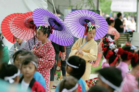 Muzak Fukuda center, and Ashley Ayano Tanaka Chu right, wait for the start of a Sakura Sakura performance during the Japan Festival Houston at Hermann Park Sunday, April 17, 2016, in Houston.
