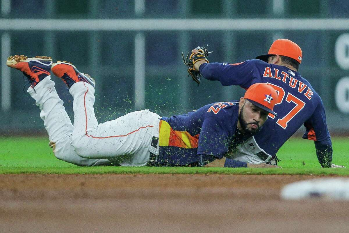 Houston Astros short stop Marwin Gonzalez (9) and Houston Astros second baseman Jose Altuve (27) collide as they go for a ground ball as the Astros take on the Tigers at Minute maid Park Sunday, April 17, 2016 in Houston.