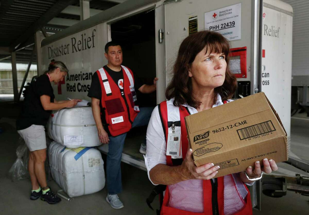 Red Cross volunteer Sharon Black, right, and Rafael Aleman, center, listen to instructions as they load storm relief items into a trailer at the American Red Cross Regional Headquarters, Sunday, April 17, 2016, in Houston.