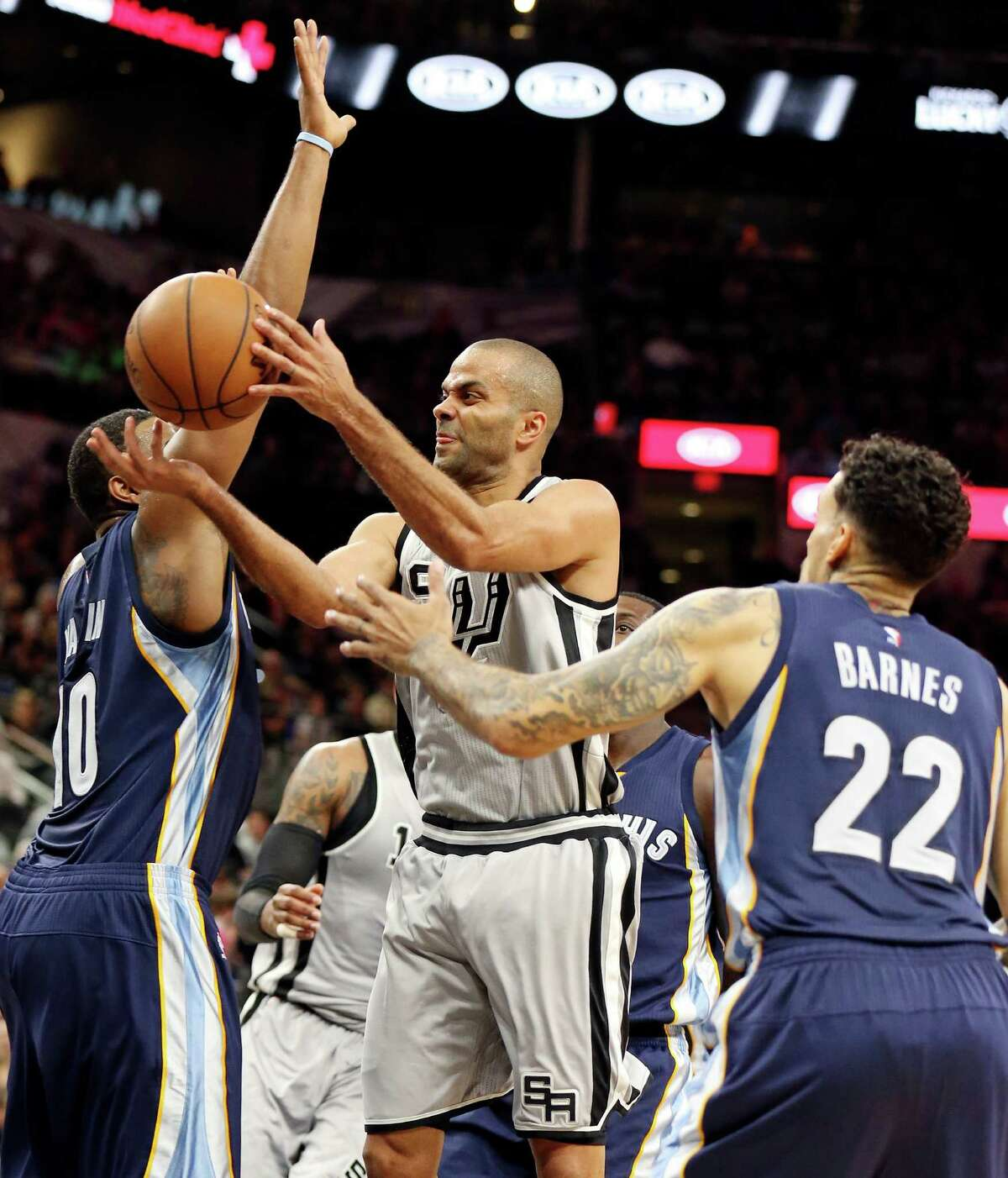 San Antonio Spurs' Tony Parker passes between Memphis Grizzlies' Jarell Martin (left) and Matt Barnes during first half action of Game 1 in the first round of the Western Conference playoffs Sunday April 17, 2016 at the AT&T Center.