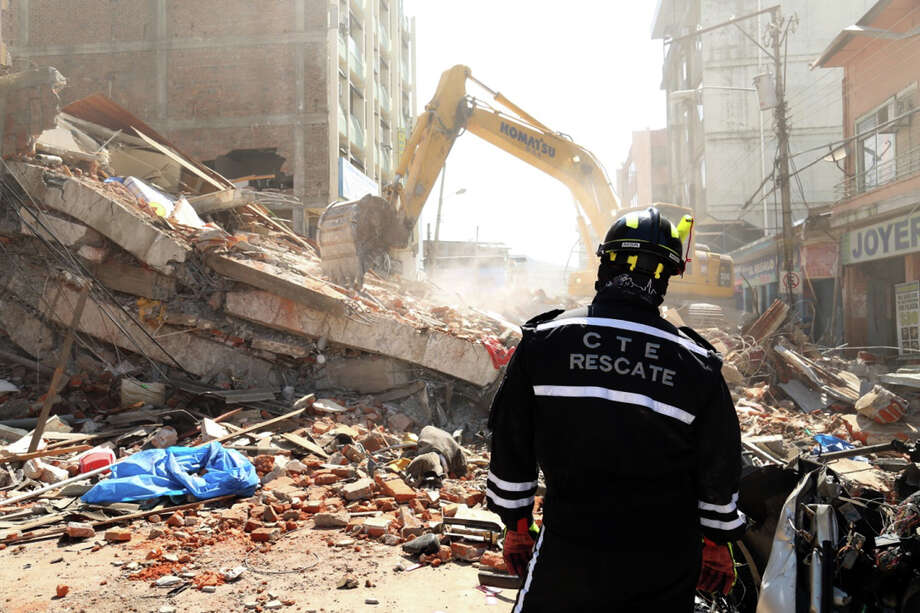 A rescue worker looks as heavy machinery removes the debris of a collapsed building in Portoviejo, Ecuador, Sunday April 17, 2016. A magnitude-7.8 quake, the strongest since 1979, hit Ecuador flattening buildings, buckling highways along its Pacific coast and killing hundreds. (AP Photo/Carlos Sacoto) Photo: Carlos Sacoto, STR / Associated Press / AP