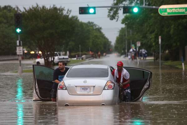 Nick Estrada helps push Jamal Reynolds car out of high water at Greens Road and Greenschase  in Houston, Monday, April 18, 2016. Heavy rains caused flooding throughout the Houston area. (Steve Gonzales/ Houston Chronicle)