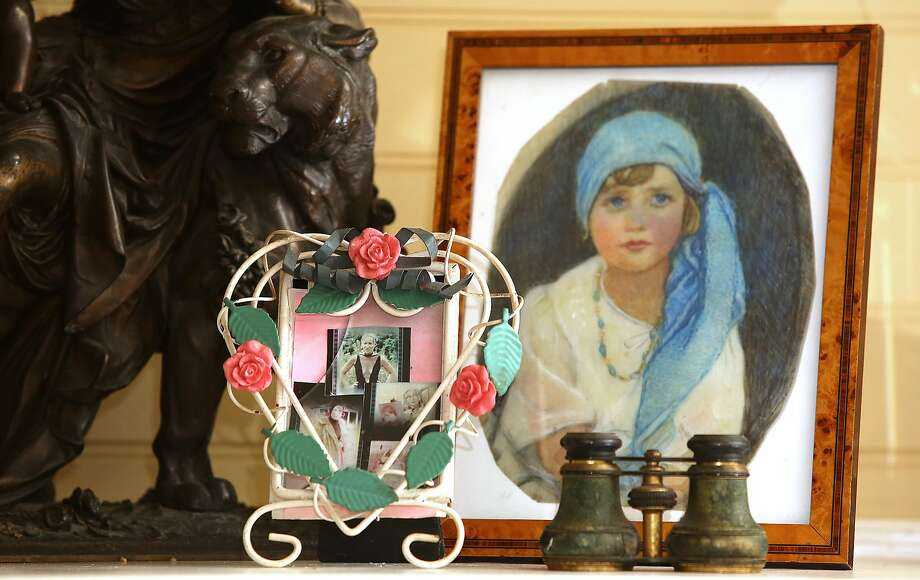"""Bouvier Beale and his wife Eva Beale display their family keepsakes on their fireplace mantel at their home in Marin County. Seen: A still of Little Edie in the documentary """"Grey Gardens,"""" a painting of Little Edie as a girl and Little Edie's opera glasses. Photo: Liz Hafalia, The Chronicle"""