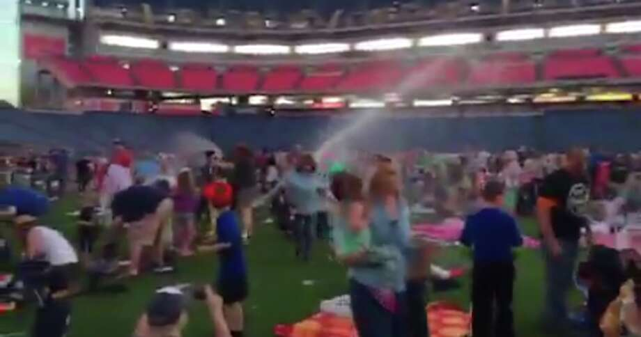 Tennessee Titans fans are sopped at an event Friday night at Nissan Stadium in Nashville when the facility's sprinkler system went off during the middle of a promotion where fans had been invited to watch a movie on the stadium's videoboard while sitting on the turf. (Twitter picture)