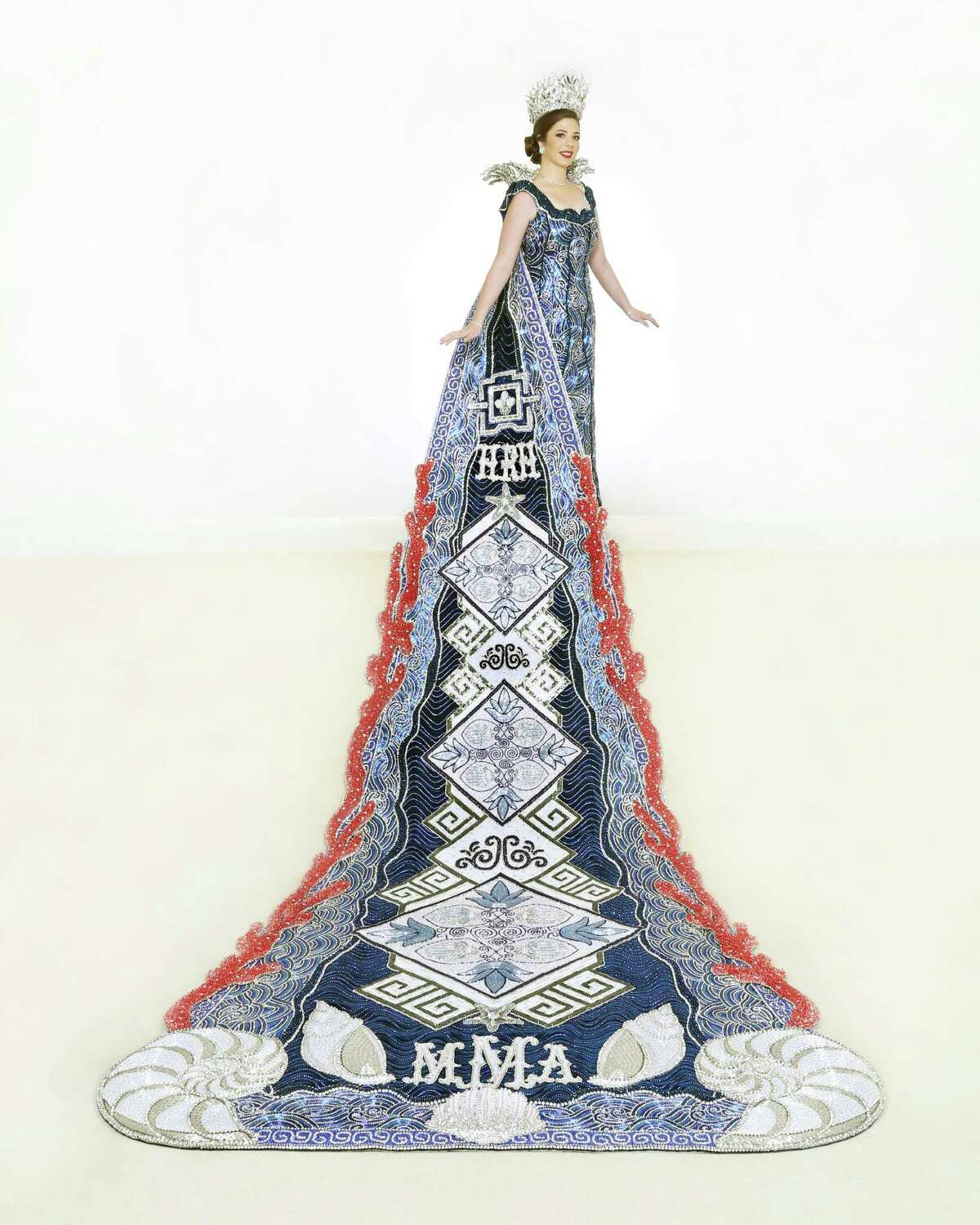 Morgan Anne McClelland, Princess of Hellenic Grandeur. Representing the Mediterranean Sea surrounding Greece, the navy blue train has a border of thick coral Swarovski crystals and features a beaded Etruscan design in white and crystal sequins with blue bugle beading. The bottom of the train has padded 3D nautilus shells. Her gown is fully beaded in a mix of blue bugle beads and chai chain to evoke the sea's ripple surrounding the Greek isles. Her crown and collar depict sea coral, enhanced with silver hues, blue Swarovski crystals and Aurora Borealis stones. She is the daughter of Mr. and Dr. Albert McClelland.