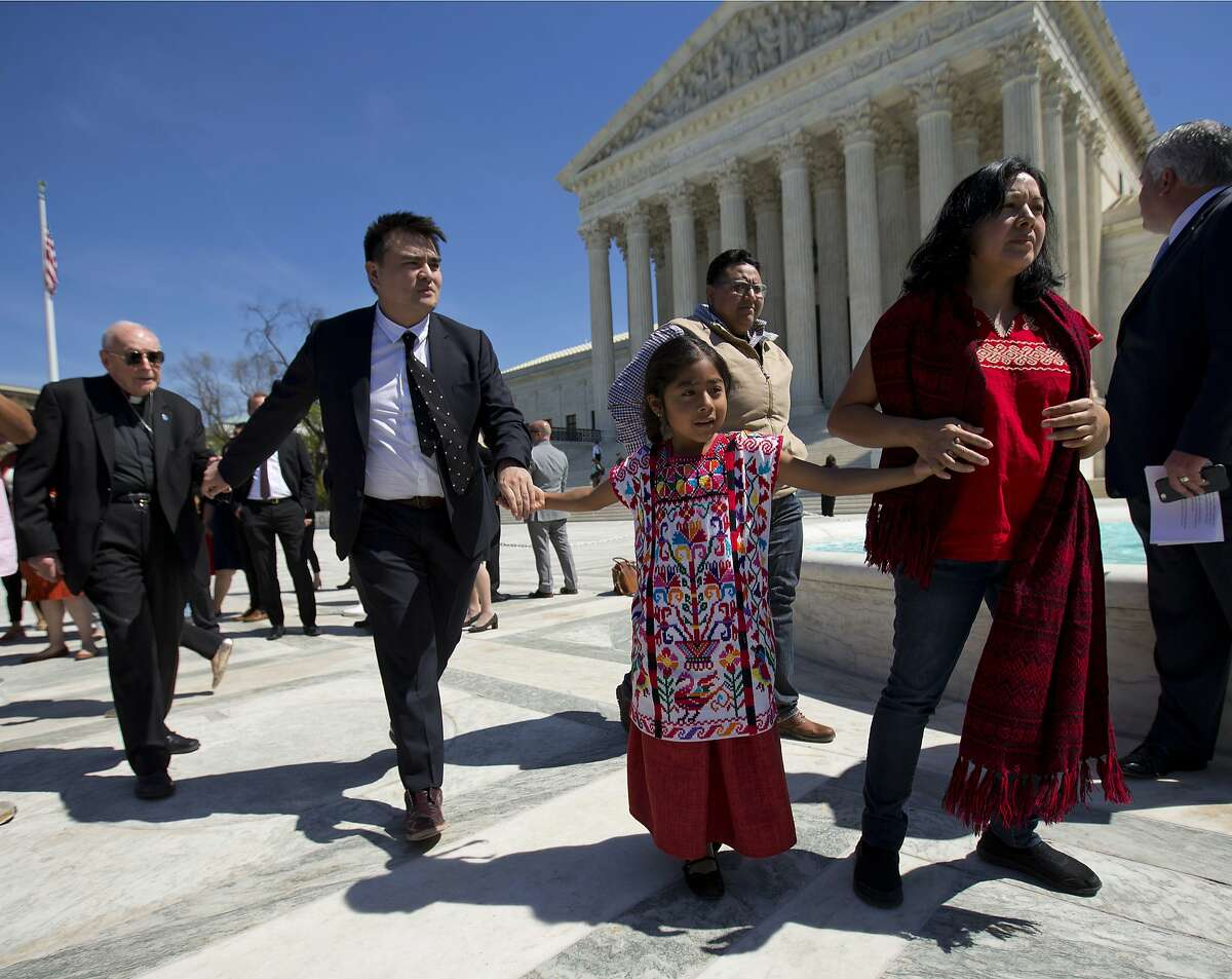 From left, Archbishop Emeritus of Washington Cardinal Theodore McCarrick, Jose Antonio Vargas, a journalist, filmmaker, and immigration rights activist from San Francisco, Sophie Cruz, 6, and her mother Zoyla Cruz, both from Los Angeles, all hold hands as they walk over to address members of the media outside the Supreme Court in Washington, Monday, April 18, 2016. The Supreme Court is taking up an important dispute over immigration that could affect millions of people who are living in the country illegally. The Obama administration is asking the justices in arguments today to allow it to put in place two programs that could shield roughly 4 million people from deportation and make them eligible to work in the United States.