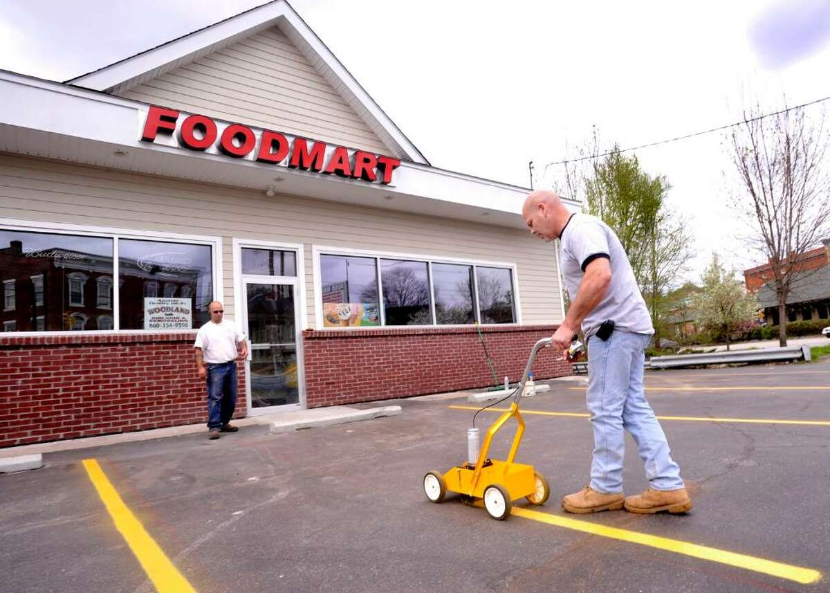 Jason Grant, left, and Leo Jette of Woodland Builders and Remodelers, paint parking lanes outside the Food Mart in New Milford on Tuesday, April 13, 2010.