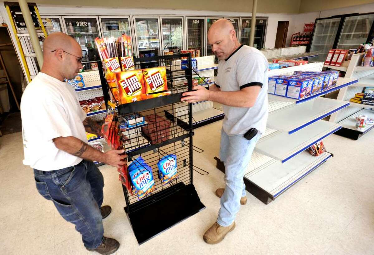 Jason Grant, left, and Leo Jette of Woodland Builders and Remodelers, move a display in the Food Mart in New Milford on Tuesday, April 13, 2010.