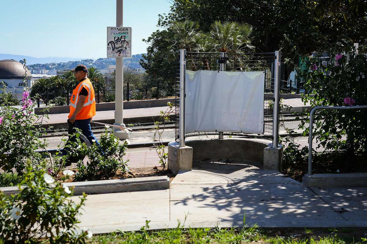 A Department of Public Works employee cleans up the area around a pissoir, which is an open-air men's toilet, on Church Street in Dolores Park, in San Francisco, California, on Monday, April 18, 2016.