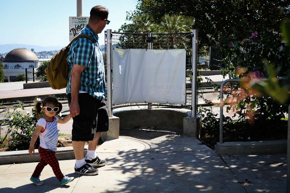 A man and child walk by a pissoir, which is an open-air men's toilet, on Church Street in Dolores Park, in San Francisco, California, on Monday, April 18, 2016.
