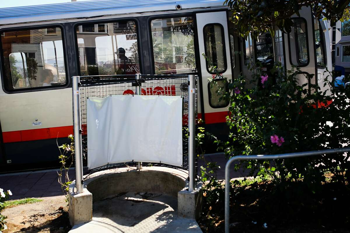 A pissoir, an open-air men's toilet, is seen as a Muni train passes behind it, on Church Street in Dolores Park, in San Francisco, California, on Monday, April 18, 2016.