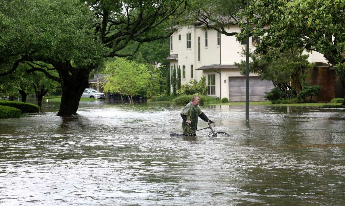 Barnie Burton walks along a flooded Chimney Rock Road, as he looks for food for his cats, after Brays Bayou flooded the Meyerland area, Monday, April 18.