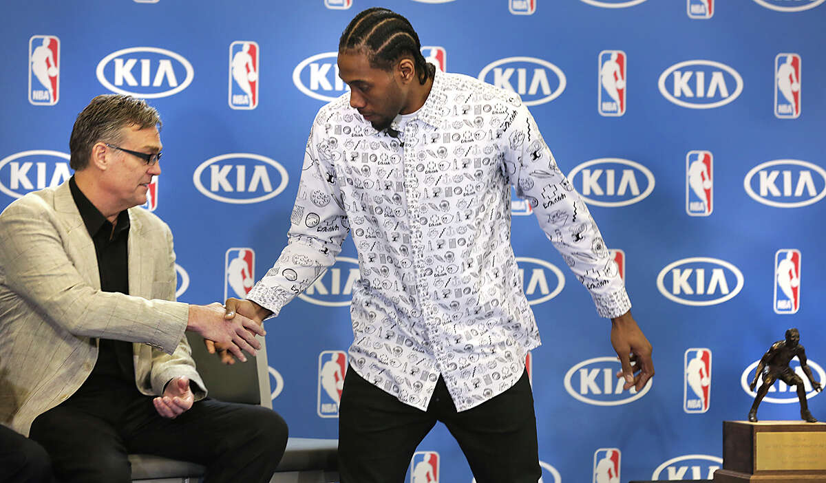 Kawhi Leonard gets a hand shake from R.C. Buford, left, General Mananger of the Spurs as he is presented the 2015-2016 NBA Defensive Player of the Year award on Monday, April 19, 2016, at the Spurs Practice Facility.