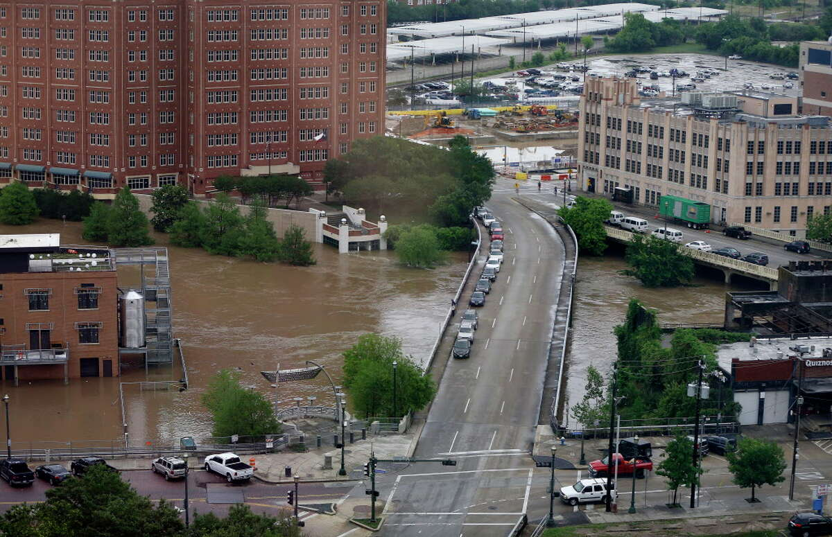 Flood waters from the Buffalo Bayou flow under the Fannin Street Bridge at Allen's Landing and the Harris County Jail, downtown, Monday, April 18, 2016, in Houston. Aerial view from the office of Robert Soard, Chief of Staff of the Harris County Attorney.