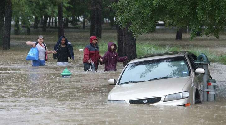 A group walk hand in hand through high water from their flooded apartment complex Monday, April 18, 2016, in Houston. ( Steve Gonzales  / Houston Chronicle  )