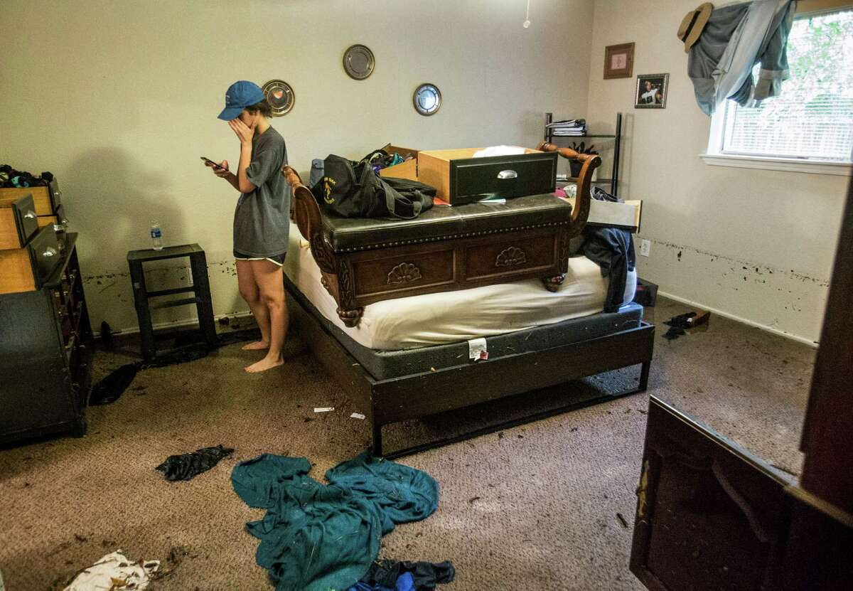 Jordan Sanchez pauses in her bedroom as she cleans up and takes pictures of the damage while cleaning up after the home was flooded in the Timber Lakes Timber Ridge subdivision on Monday, April 18, 2016, in The Woodlands. ( Brett Coomer / Houston Chronicle )