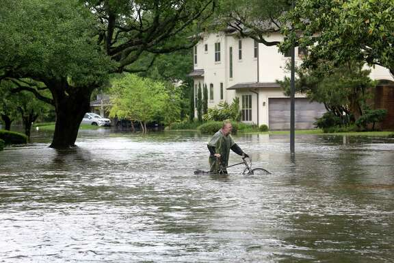Barnie Burton walks along a flooded Chimney Rock Road, as he looks for food for his cats, after Brays Bayou flooded the Meyerland area, Monday, April 18, 2016, in Houston.  ( Jon Shapley / Houston Chronicle )