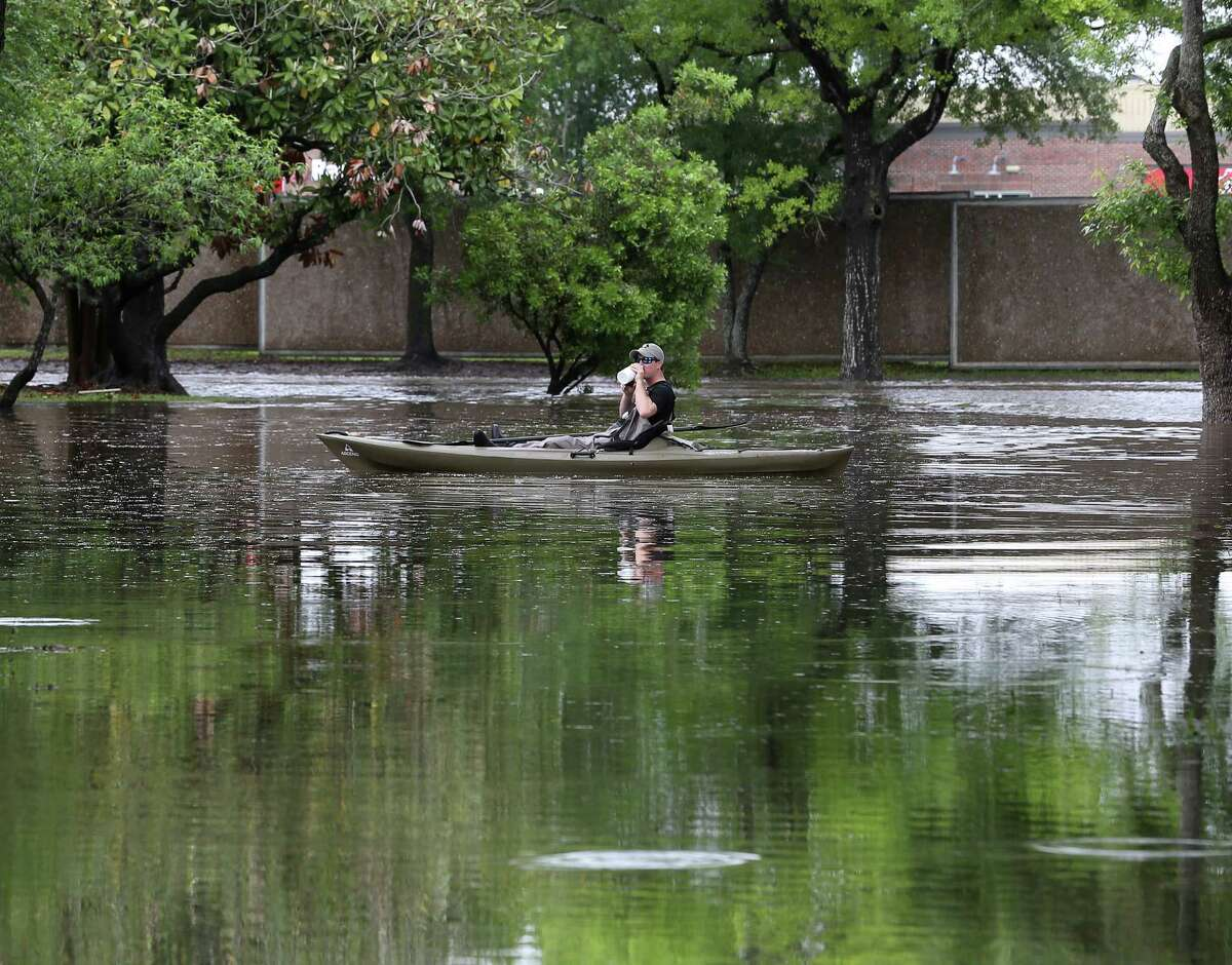 A kayaker pauses for water before kayaking along Wigton Drive, in the Meyerland area, Monday, April 18, 2016, in Houston. ( Jon Shapley / Houston Chronicle )
