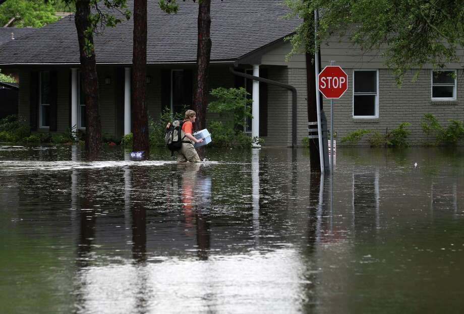 A man carries a pet carrier and other belongings through flood water, along Runnymeade Drive, in the Meyerland area, Monday, April 18. Photo: Jon Shapley, Jon Shapley/Houston Chronicle / © 2015  Houston Chronicle