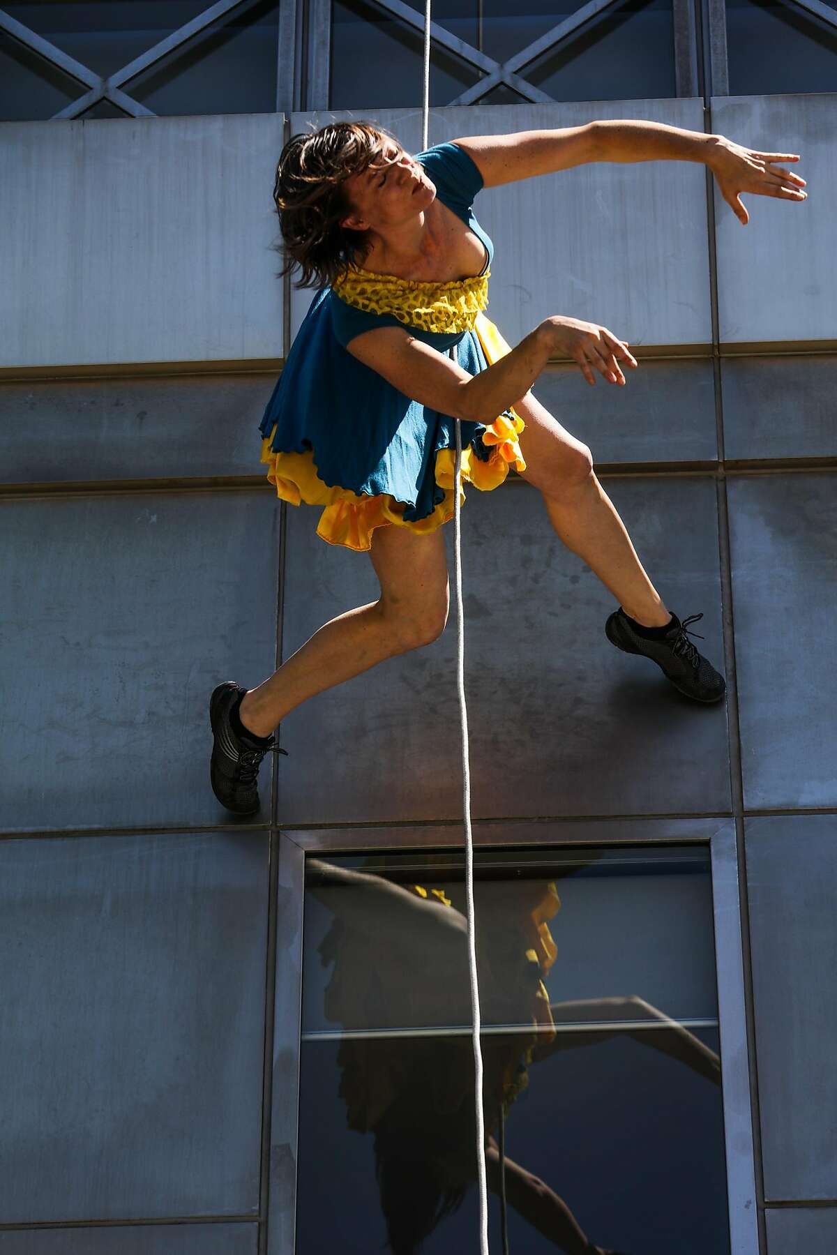 A member of BANDALOOP performs a vertical dance on the side of the San Francisco Public Library, to celebrate the 20th anniversary of the library, in San Francisco , California, on Monday, April 18, 2016.