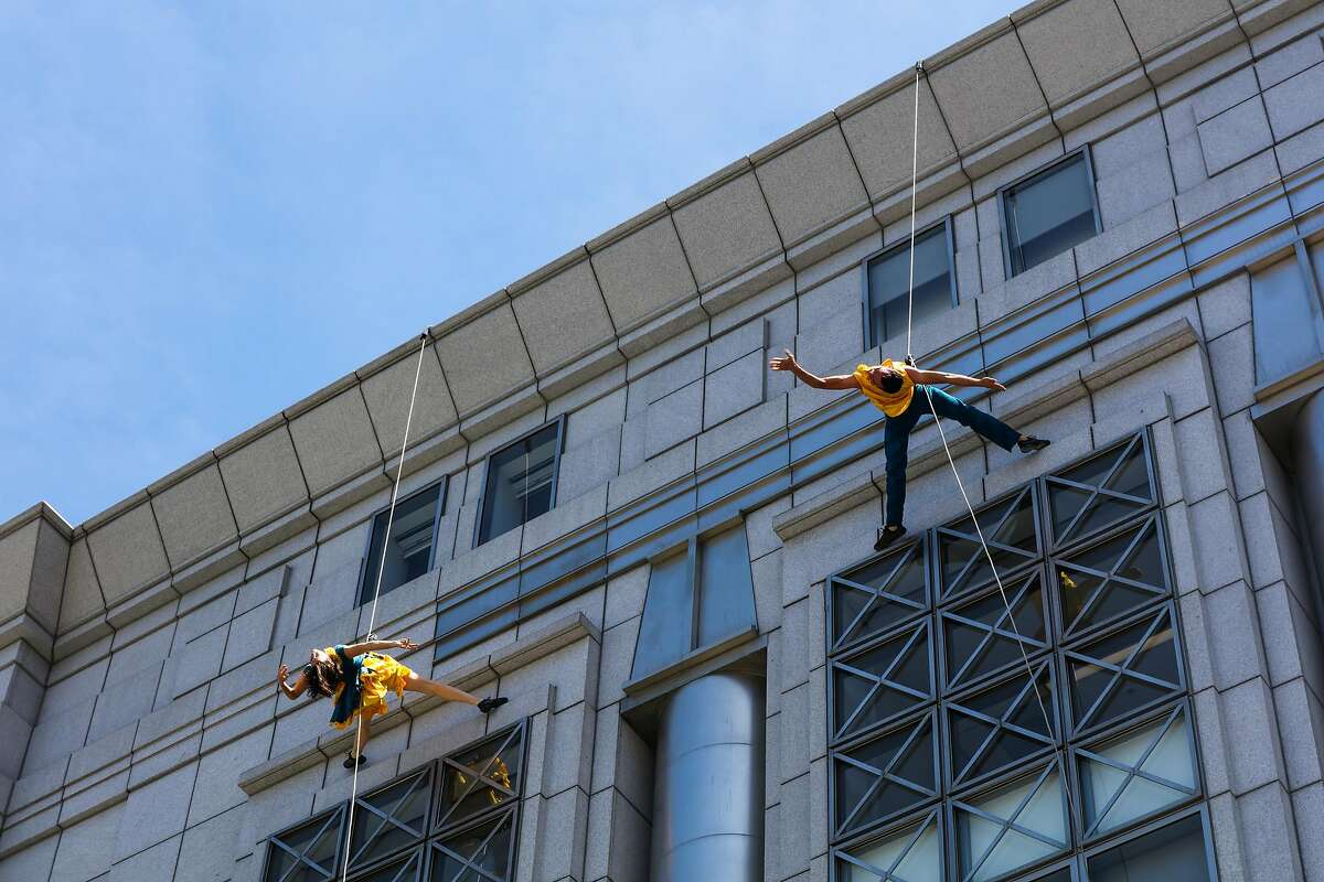 Members of BANDALOOP perform a vertical dance on the side of the San Francisco Public Library, to celebrate the 20th anniversary of the library, in San Francisco , California, on Monday, April 18, 2016.