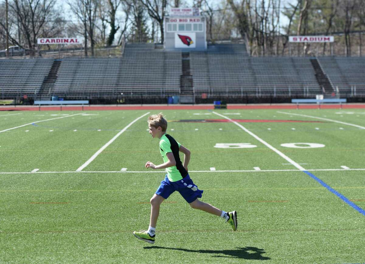 Owen Morrissey, 11, of Byram, runs on the artificial turf playing surface at Greenwich High School's Cardinals Stadium field in Greenwich, Conn. Thursday, April 14, 2016. School officials met at Cardinal Stadium Thursday with prospective bidders for the replacement of the turf at the stadium.