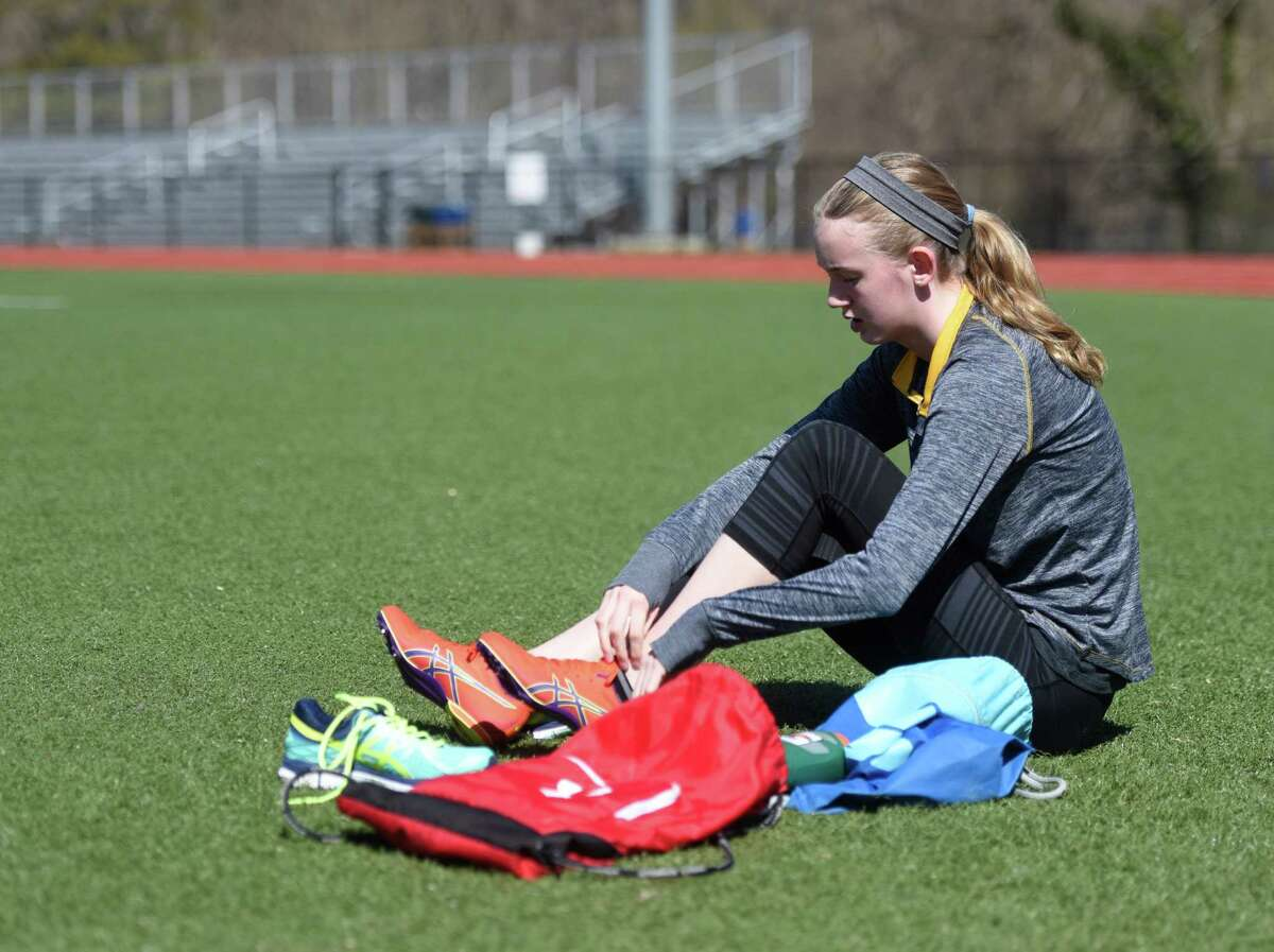 Ella Morrissey, a freshman on the GHS track team, puts on running shoes on the artificial turf playing surface at Greenwich High School's Cardinals Stadium field in Greenwich, Conn. Thursday, April 14, 2016. School officials met at Cardinal Stadium Thursday with prospective bidders for the replacement of the turf at the stadium.