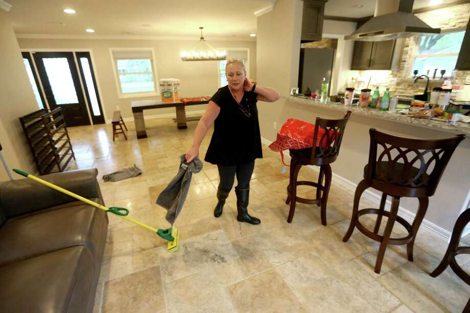 Marla Cooper removes floodwater from her home Monday along the 5900 block of Reamer Street. Cooper's home was flooded last May. She moved her new furniture in on Saturday and hadn't even spent the night at her house before it flooded again Monday. Photo: Gary Coronado, Staff / © 2015 Houston Chronicle