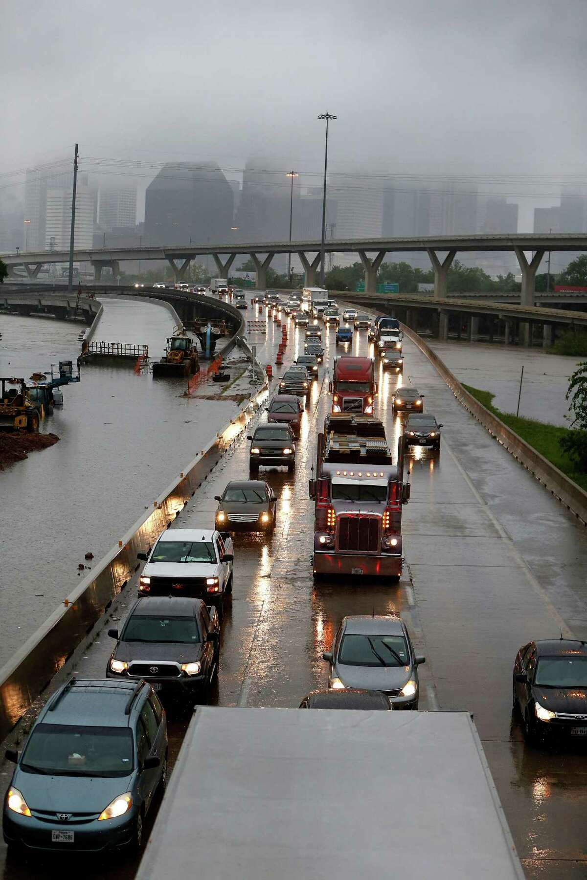 Cars creep north on I-45 North as floodwaters surround them near downtown at Quitman Street as White Oak Bayou came out of its banks Monday.
