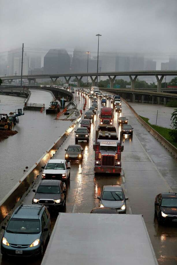 Cars creep north on I-45 North as floodwaters surround them near downtown at Quitman Street as White Oak Bayou came out of its banks Monday. Photo: Karen Warren, Staff / © 2016 Houston Chronicle