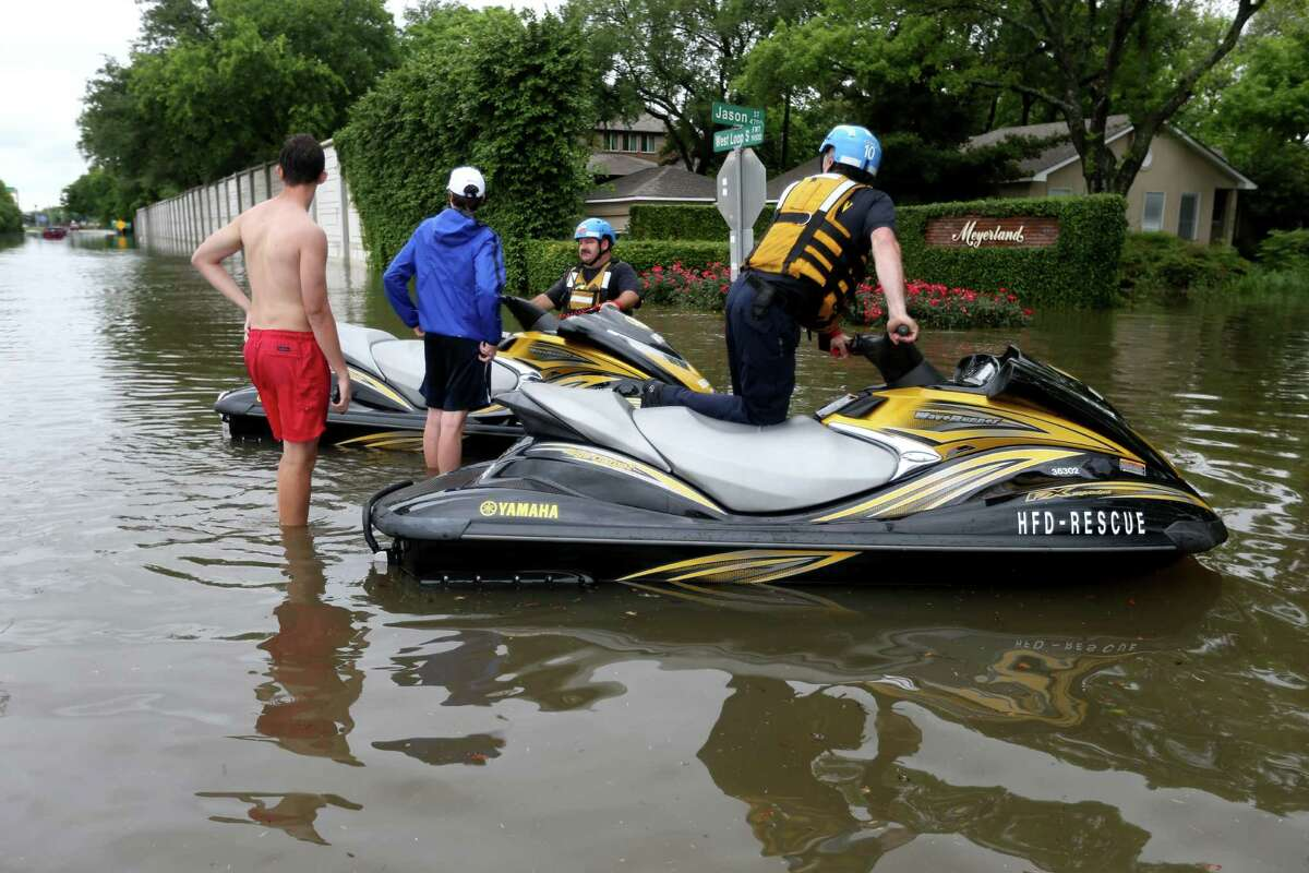 Houston Fire Department personnel use watercraft to navigate the flooded Meyerland neighborhood Monday along West Loop South at Jason Street.