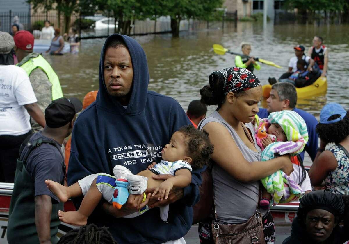 People evacuate from Arbor Court Apartments in the Greenspoint area Monday, April 18, 2016, in Houston.