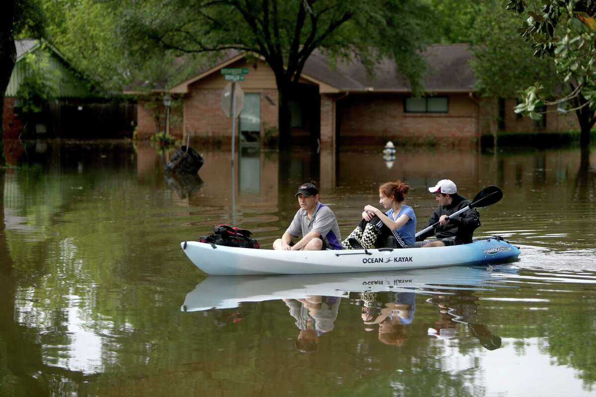 Gideon Miller, Natanya Abramson and Yari Garner canoe along the 9300 block of Greenwillow in the flooded Willow Meadows neighborhood on Monday, April 18. (For more photos of the flood, scroll through the gallery.)