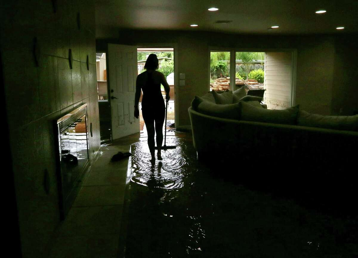 Meital Harari pushes water out the back door at her Meyerland home, Monday, April 18. (For more photos from the Tax Day flood, scroll through the gallery.)