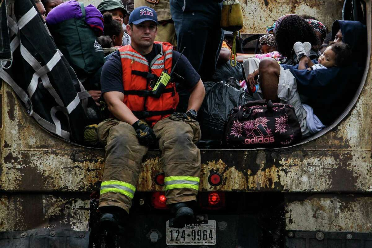 A woman holds her child as firefighters evacuate people from the flooding in the Greenspoint area in dump trucks Monday, April 18, 2016 in Houston.