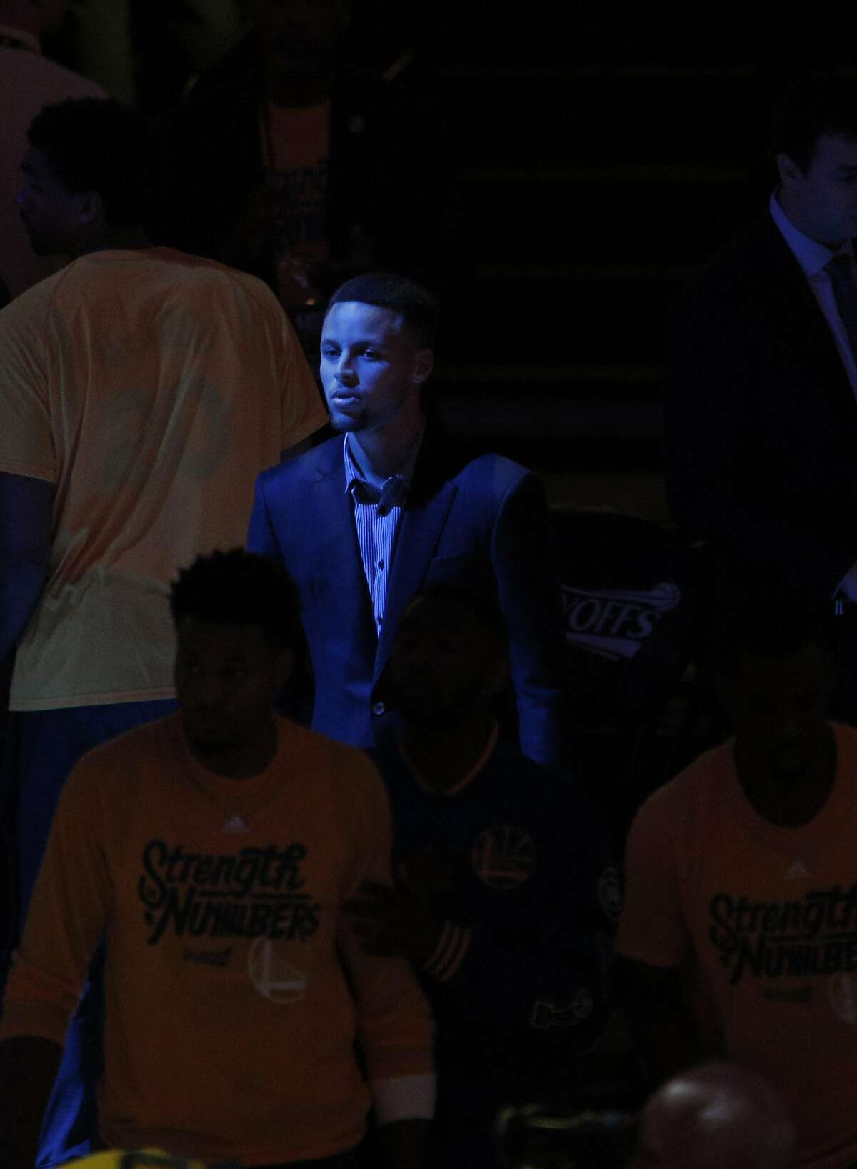 Stephen Curry (30) with the team but in his street clothes during introductions before the first half as the Golden State Warriors played the Houston Rockets in game 2 of the first round of the Western Conference Playoffs at Oracle Arena in Oakland, Calif., on Monday, April 18, 2016.