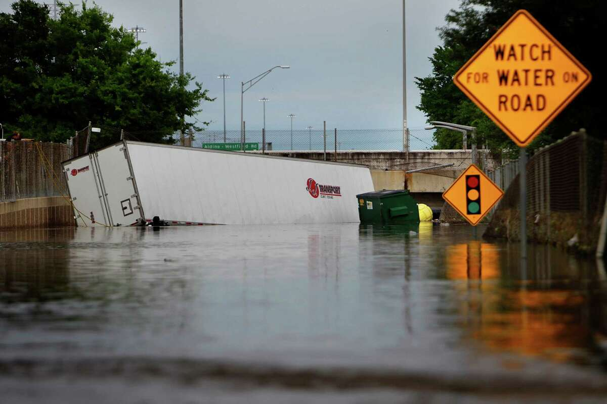 A truck is shownpartially submerged along the Beltway 8 feeder road near Hardy Road on Monday.