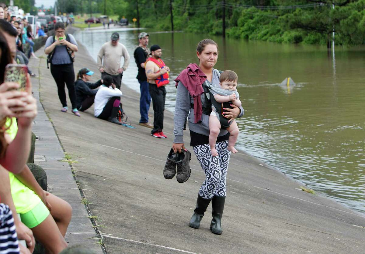 With a baby, a woman carries the shoes of her partner, who rushed to help rescue horses on Cypresswood Drive along Cypress Creek on Monday.